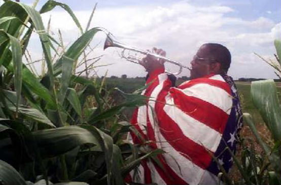 Rev. Ronald V. Myers, Sr., M.D. Chairman, National Juneteenth Holiday Campaign playing the trumpet in a corn field