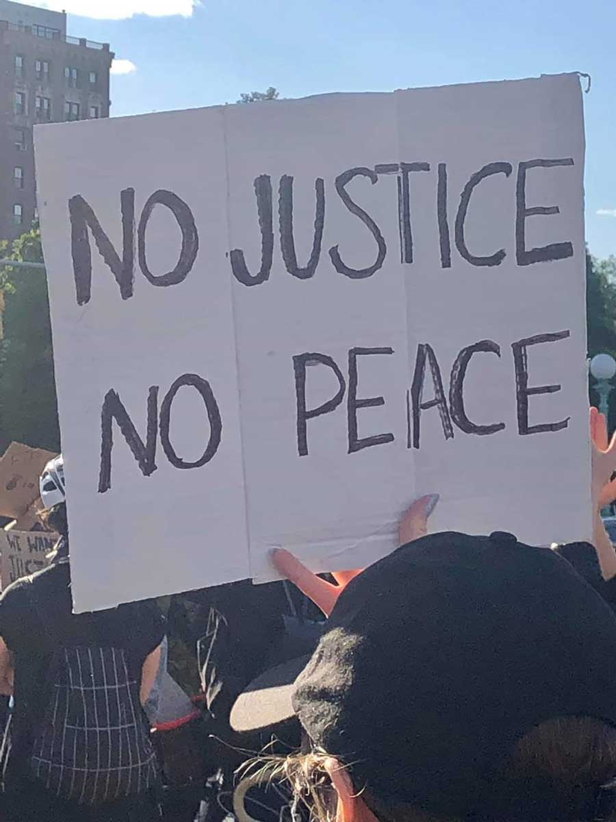"Protest with sign saying ""No justice no peace"""