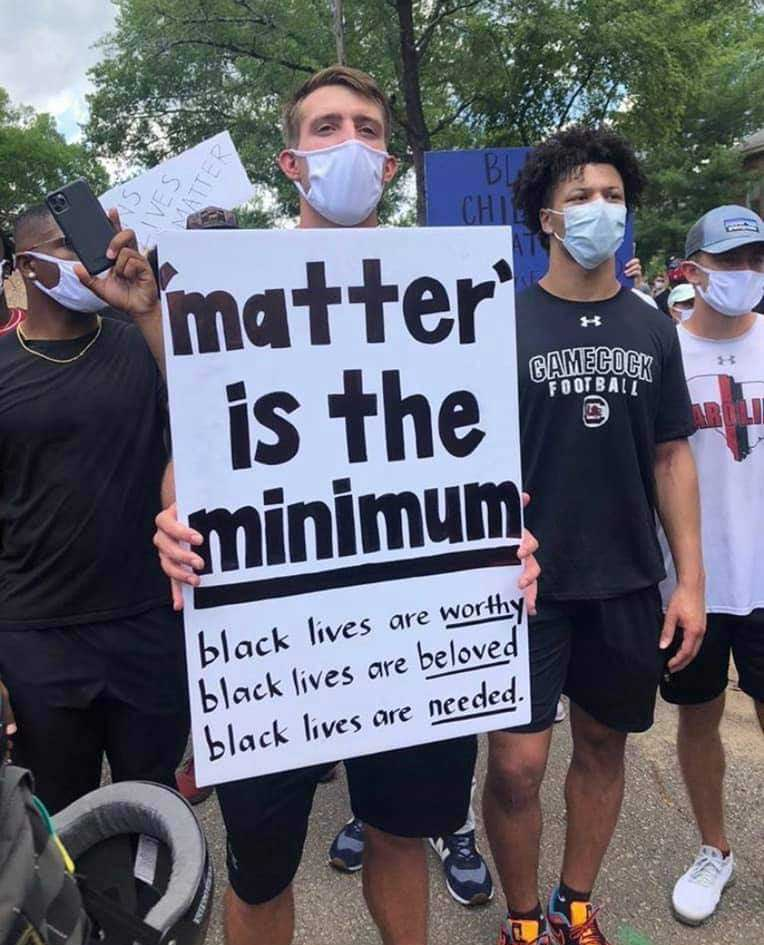 "Group of Black Lives Matter Protesters with sign that says ""'matter' is the minimum: black lives are worty, black lives are beloved, black lives are needed."""