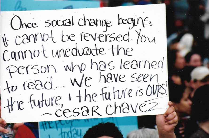 Person holding sign with Cesar Chavez quote
